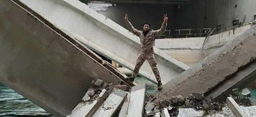 """Ein """"Rebell"""", """"Aufständischer"""", """"Oppositioneller"""" – so das Wording der westlichen Propaganda- triumphiert in den Trümmern der zerstörten Wasserversorgung von Wadi Barada. Eines von vielen Kriegsverbrechen gegen die Zivilbevölkerung in Damaskus. (Quelle)"""